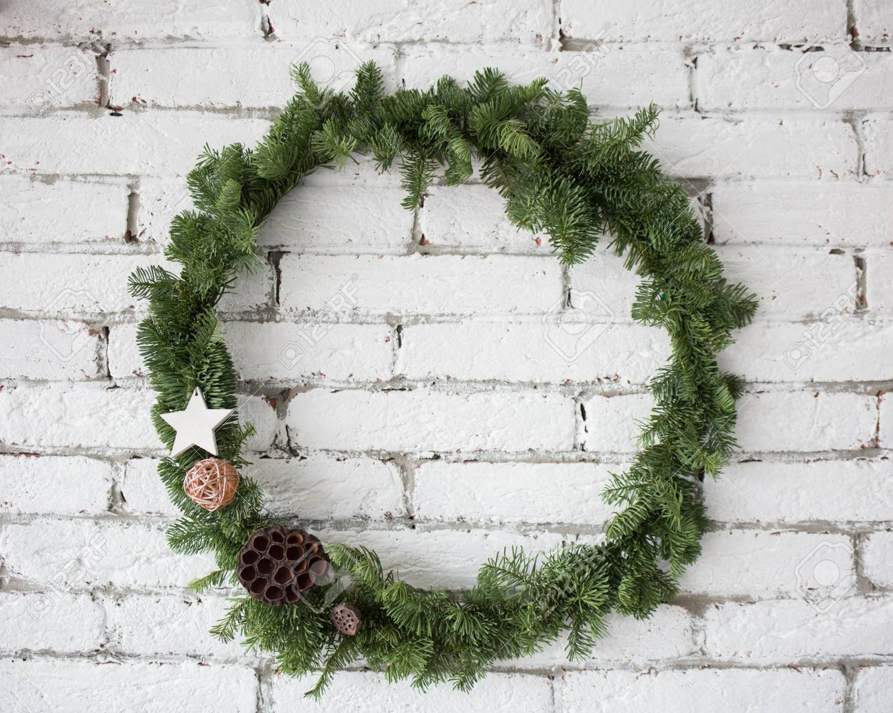 closeup view of round elegant christmas wreath hanging on white brick wall wreath decorated with