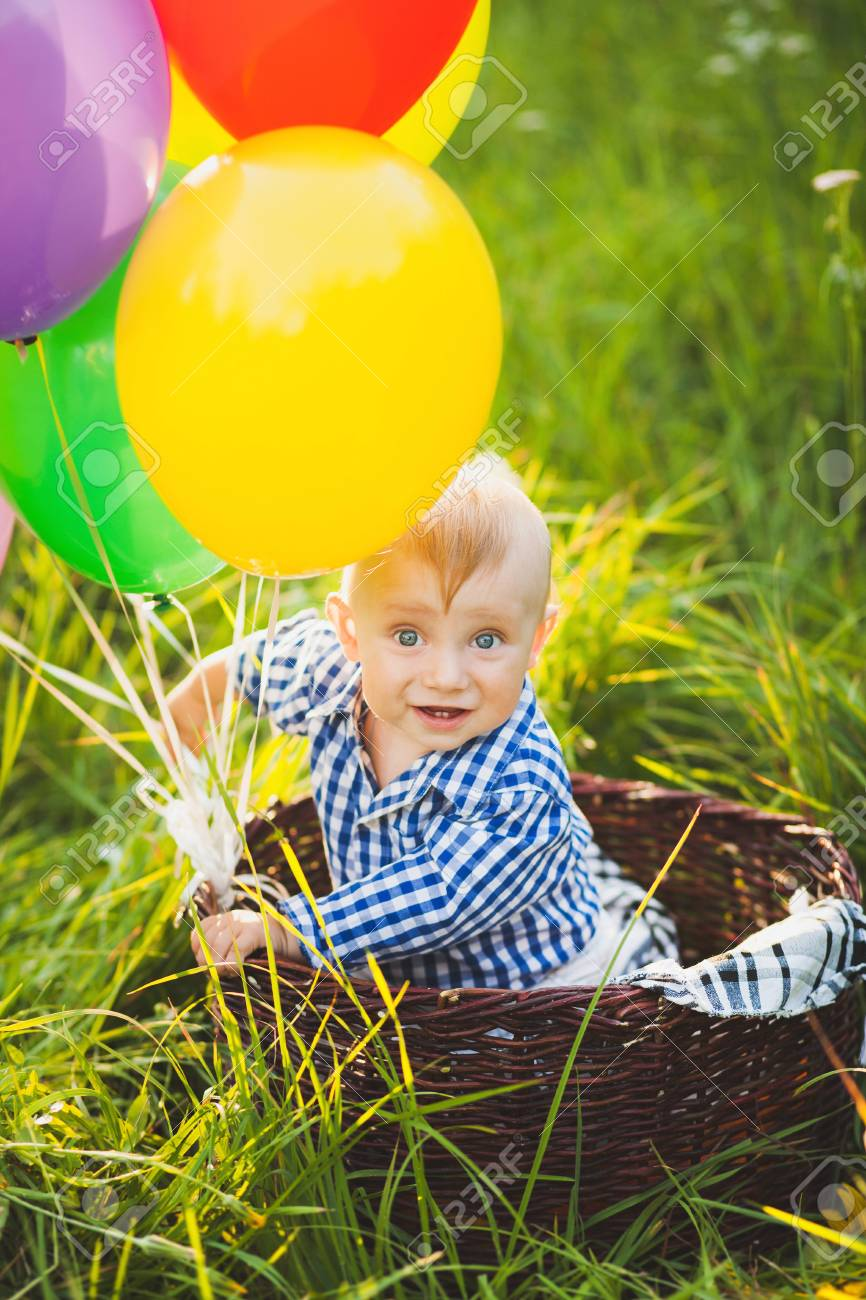 8c61daeac3bb Beautiful funny little child wearing blue shirt sitting at basket decorated  with colorful air balloons at