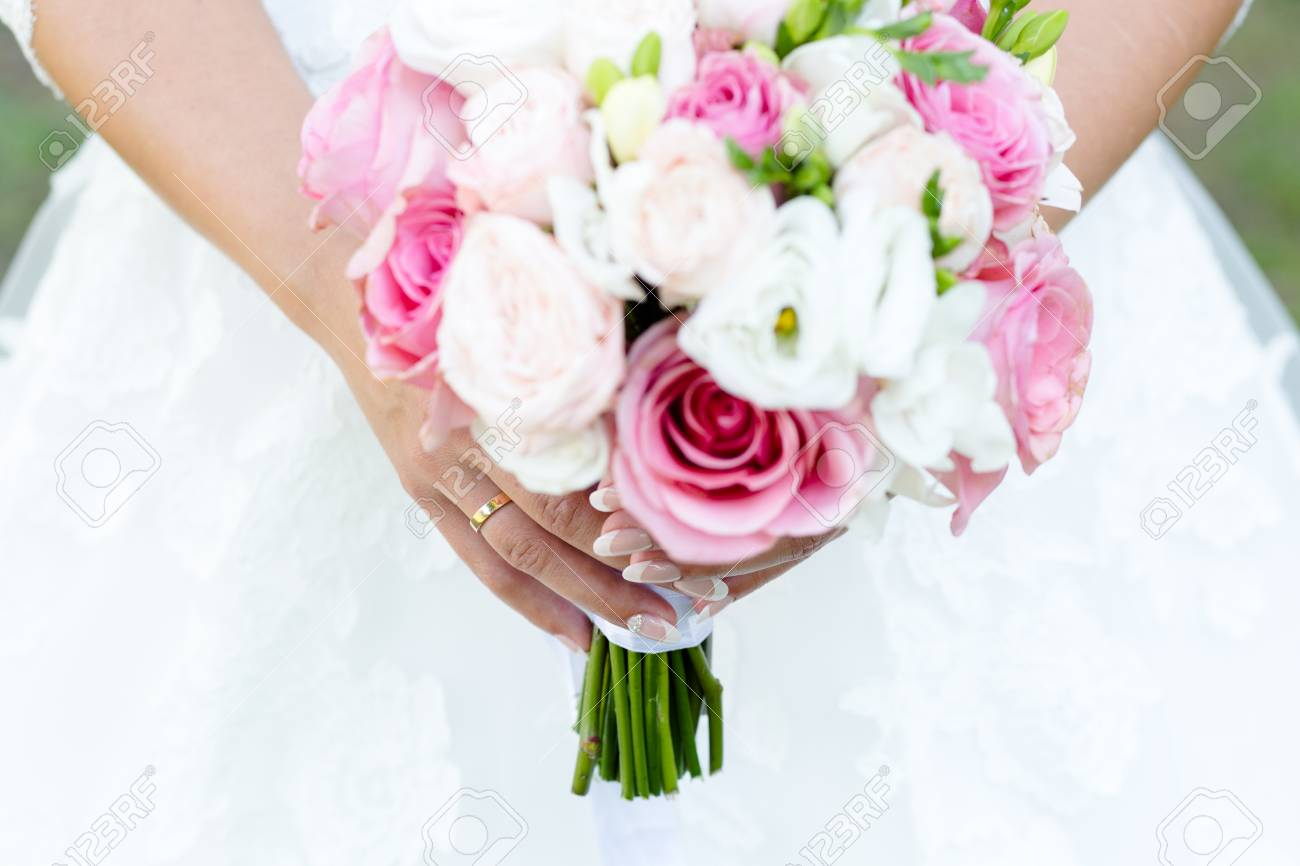 Wedding bouquet of roses and freesias in the hands of the bride - 122942756