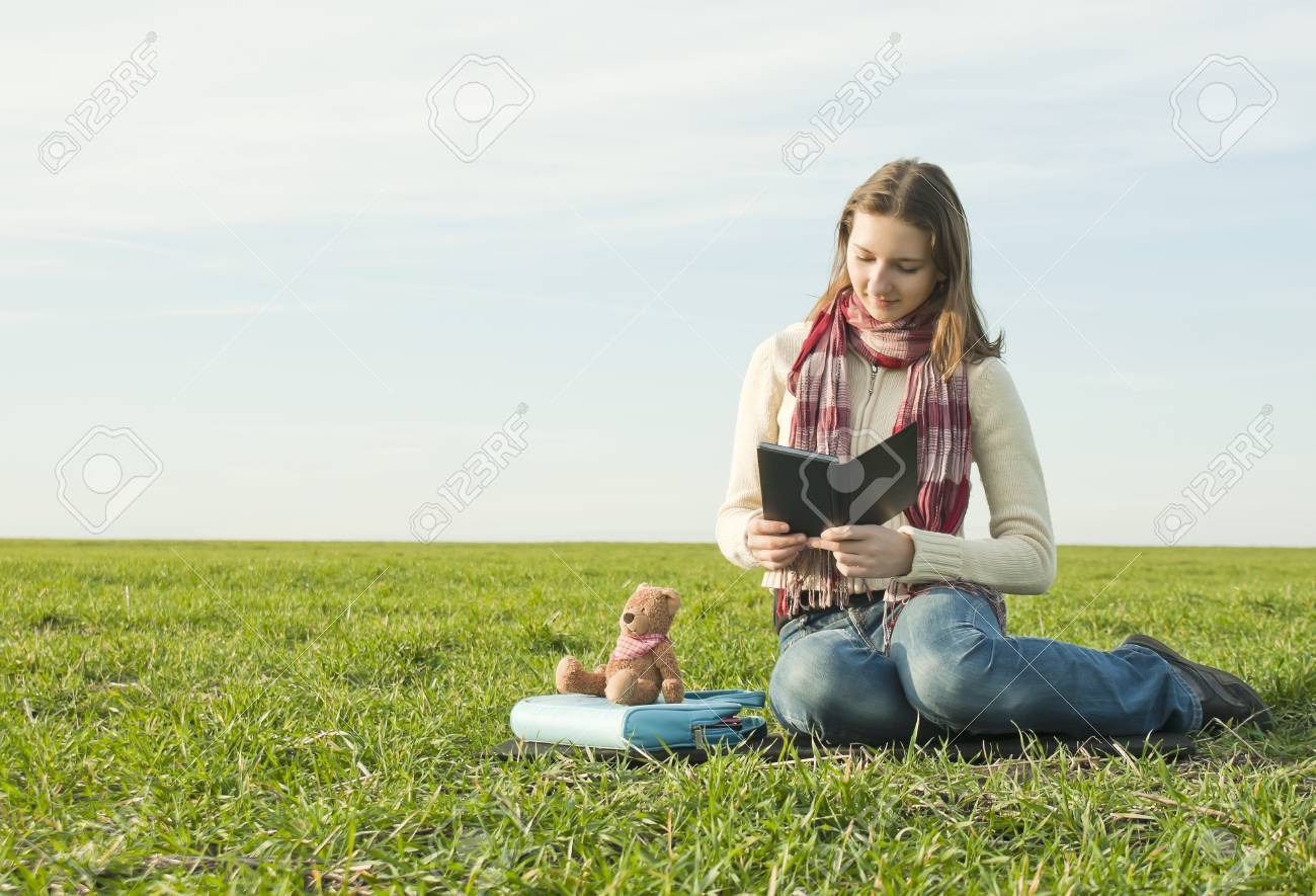 Girl reading a ebook sitting at grass Stock Photo - 8926347