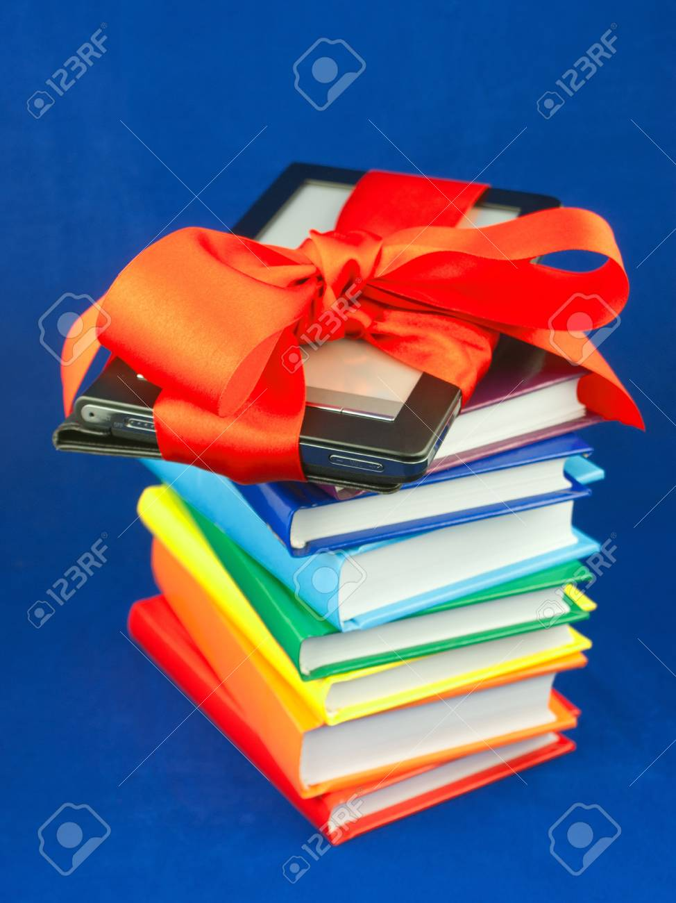 Electronic book reader tied up with red ribbon on the stack of books Stock Photo - 10612476
