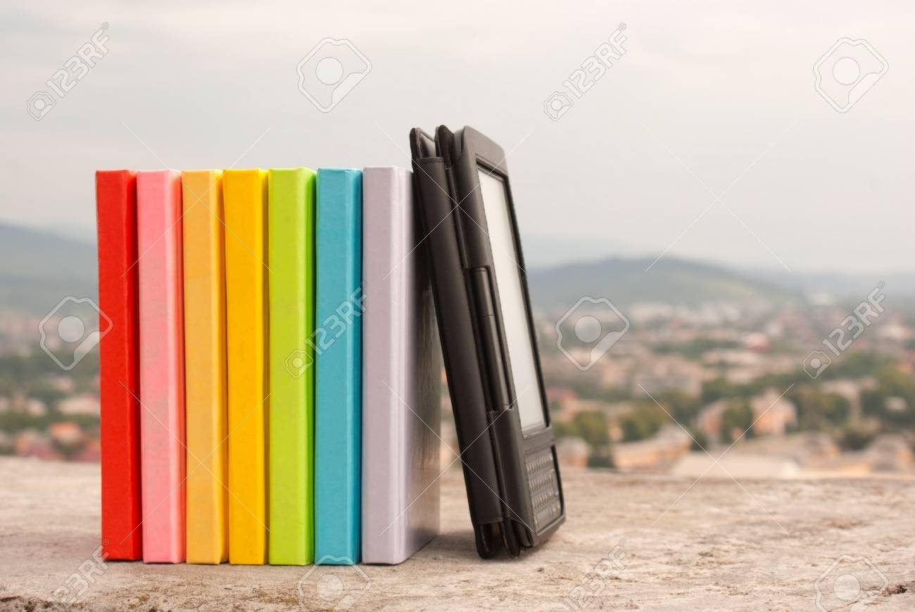 Row of colorful books with electronic book reader Stock Photo - 10879307