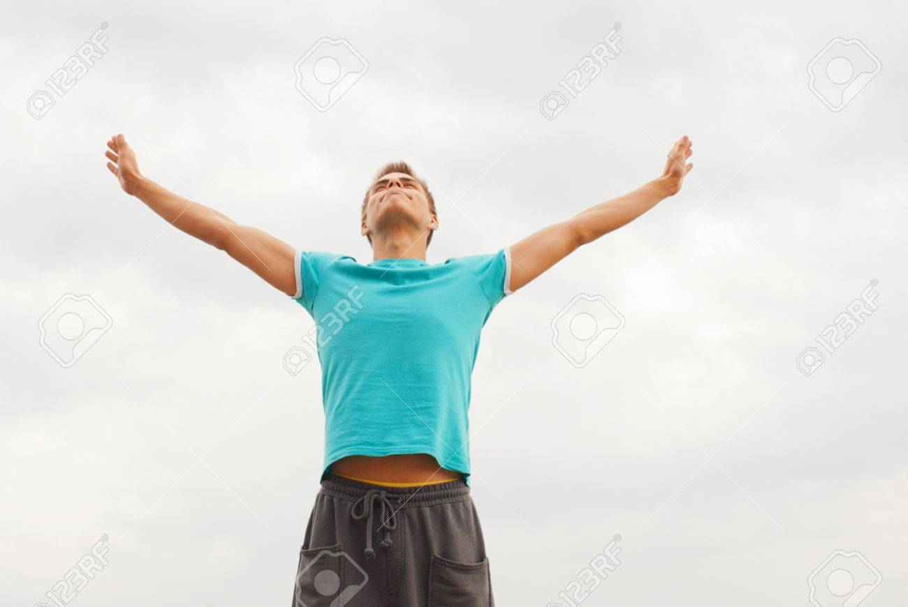 Young man staying with raised hands against blue sky Stock Photo - 11370057
