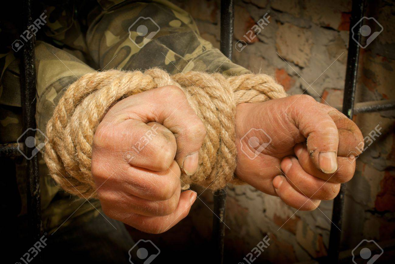 Man with hands tied with rope behind the bars Stock Photo - 12520216