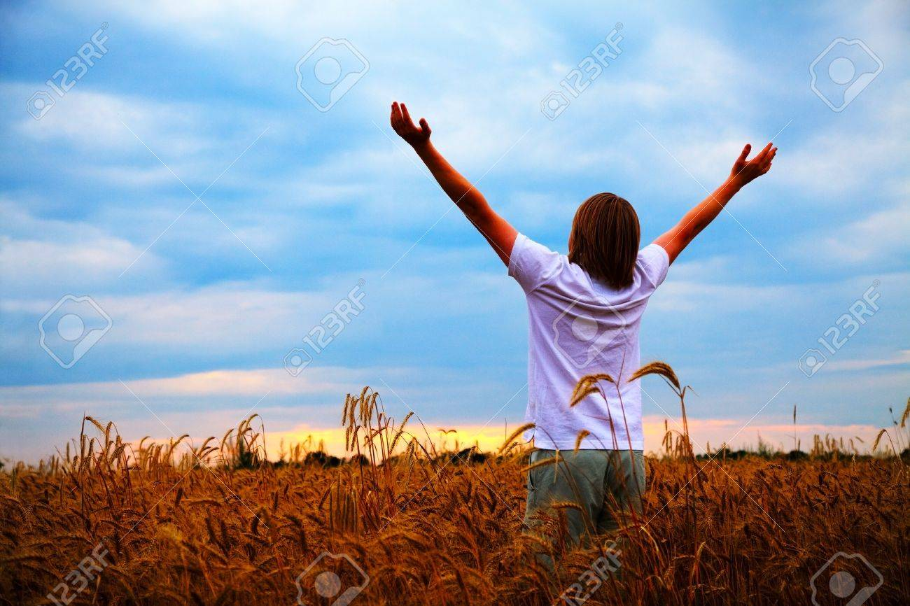 Young man staying with raised at wheat field hands at sunset time - 14276910