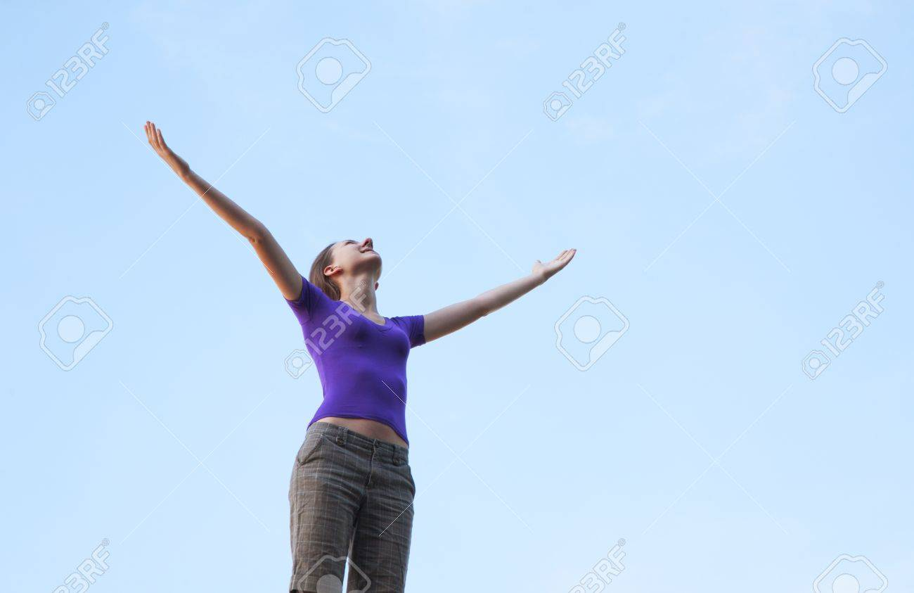 Young woman staying with raised hands against blue sky Stock Photo - 14656019