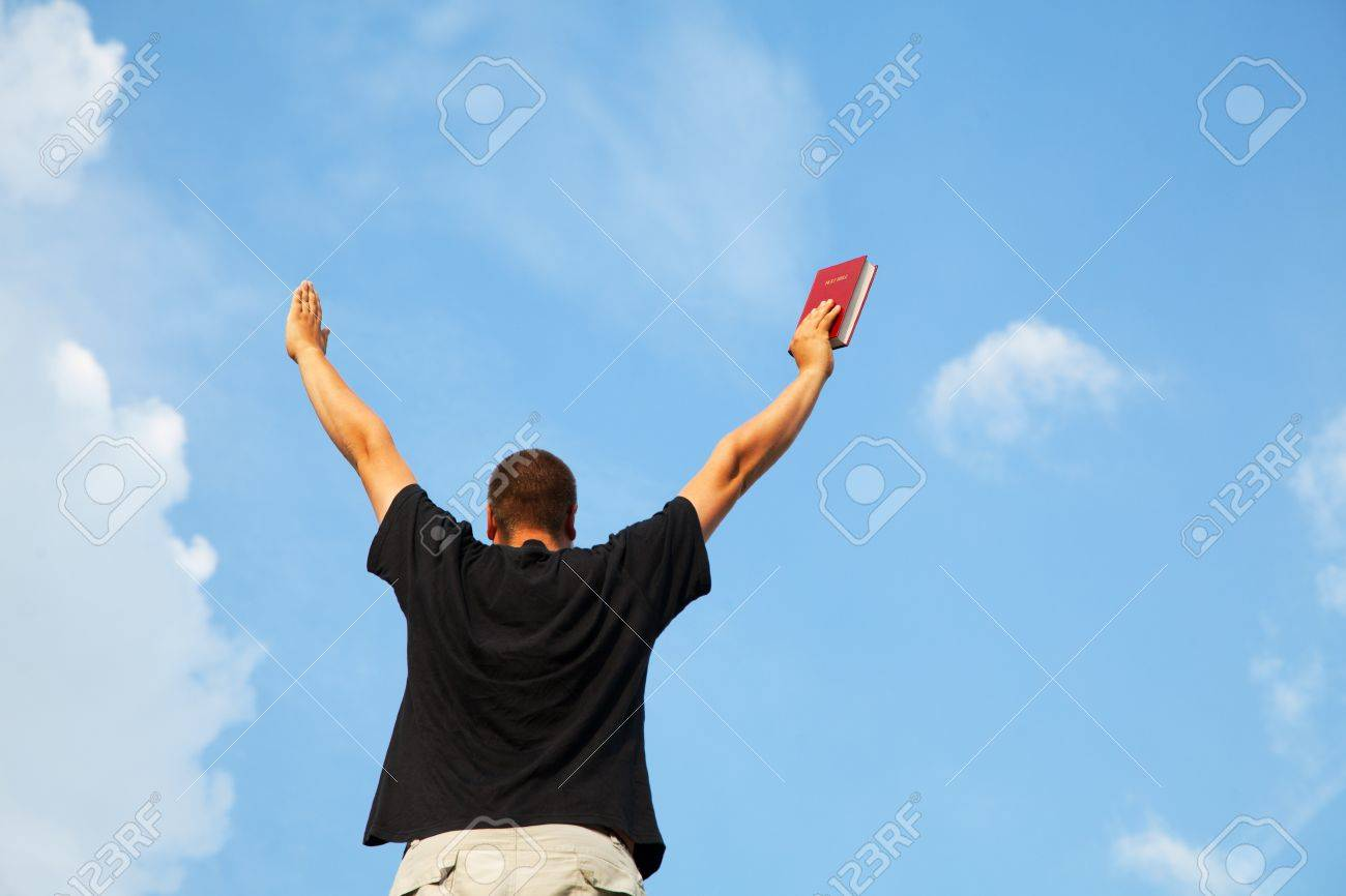 Young man staying with raised hands against blue sky Stock Photo - 14656030