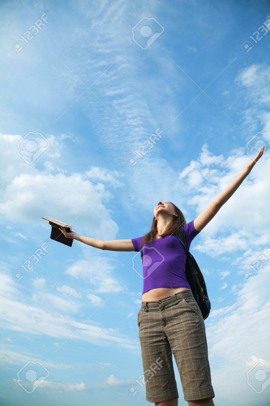 Young woman staying with raised hands against blue sky Stock Photo - 14656045