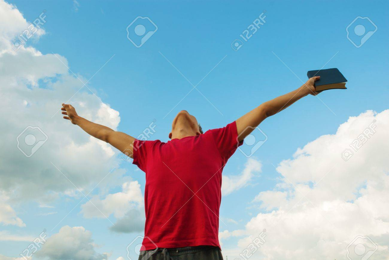 Young man staying with raised hands against blue sky Stock Photo - 18820740