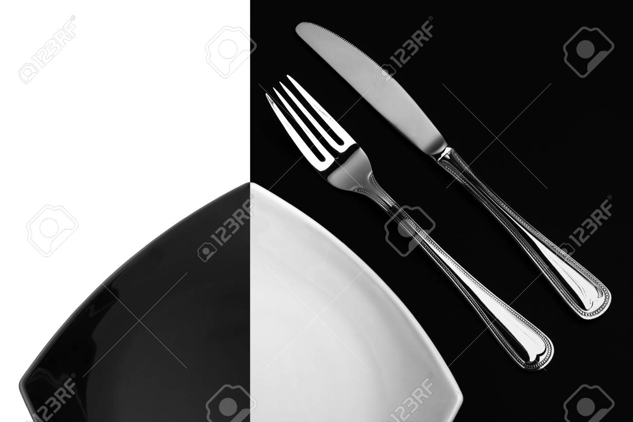 Knife, square white plate and fork on black background Stock Photo - 6021332