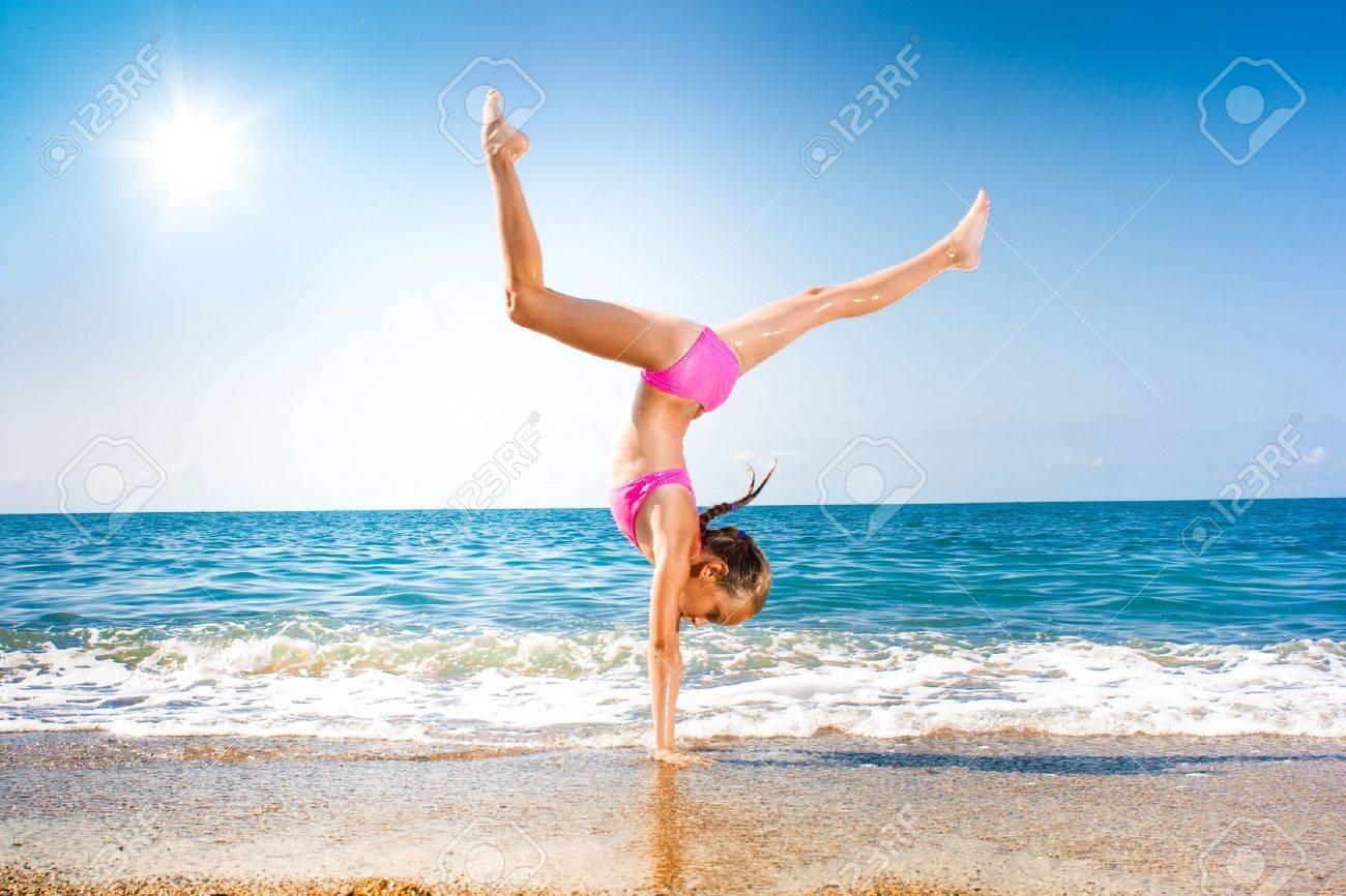 schoolgirl making gymnastics on seashore Stock Photo - 7873028