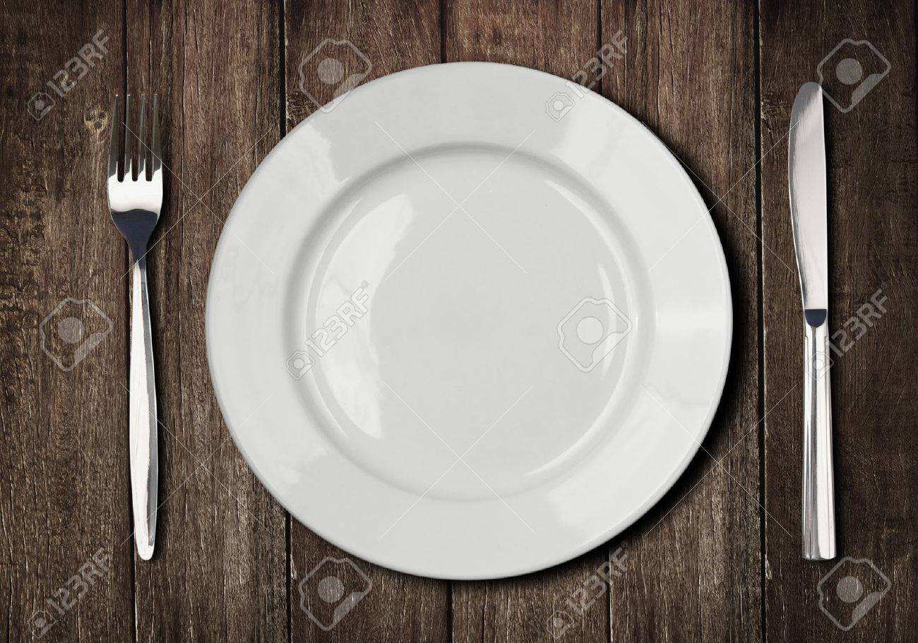 White Plate, Knife And Fork On Old Wooden Table Stock Photo ...