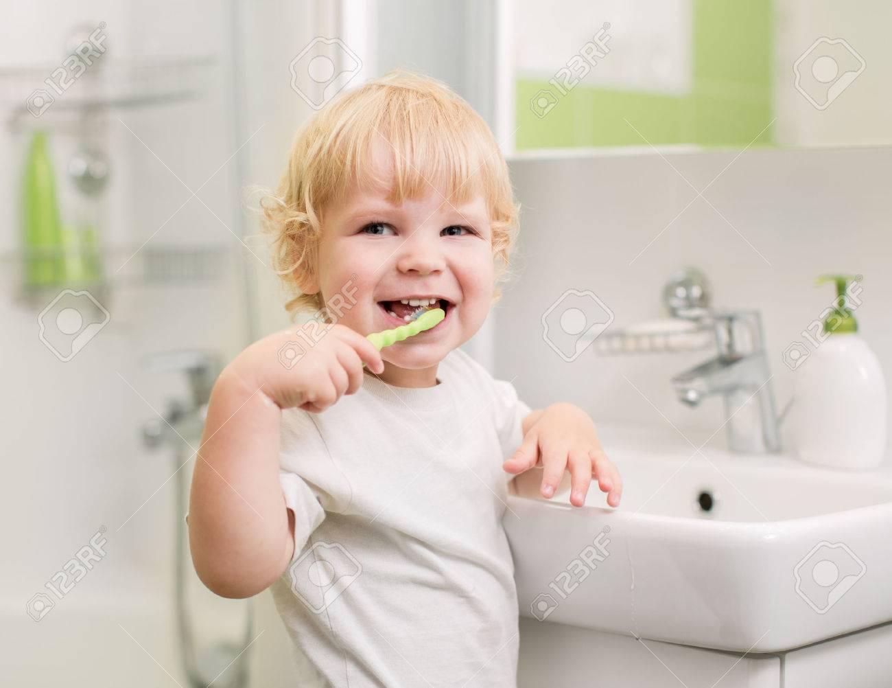 Happy kid brushing teeth Stock Photo - 22273559