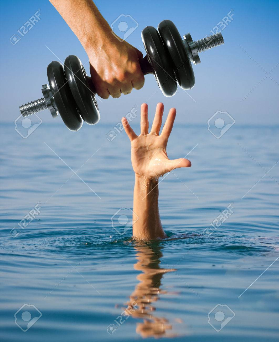 Giving dumbbell to sinking man instead of help making worse concept stock photo 28608796