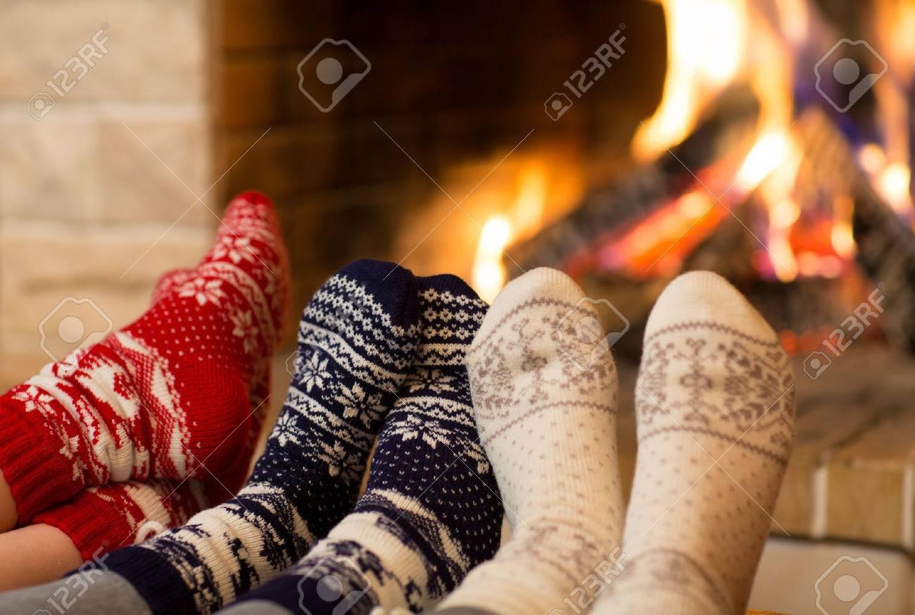Feet in wool socks near fireplace in winter time - 49176722