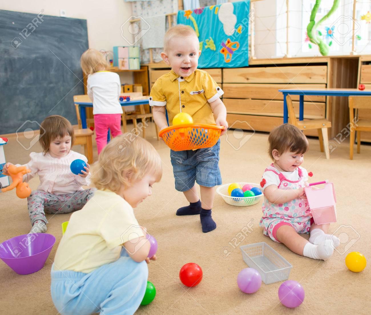 Grupo De Ninos Jugando Con Las Bolas En Jardin De Infancia O