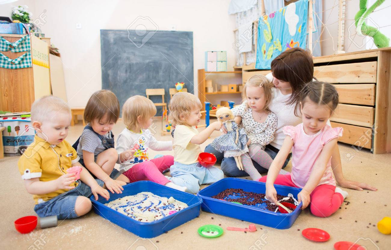 Group of children and nurse playing with rice and beans in kindergarten or day care centre - 56494598