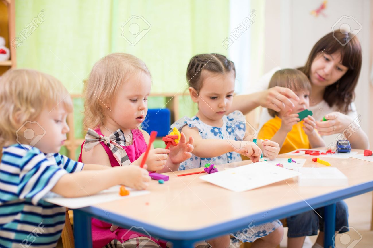 kids group learning with teacher arts and crafts in day care centre playroom - 56494603
