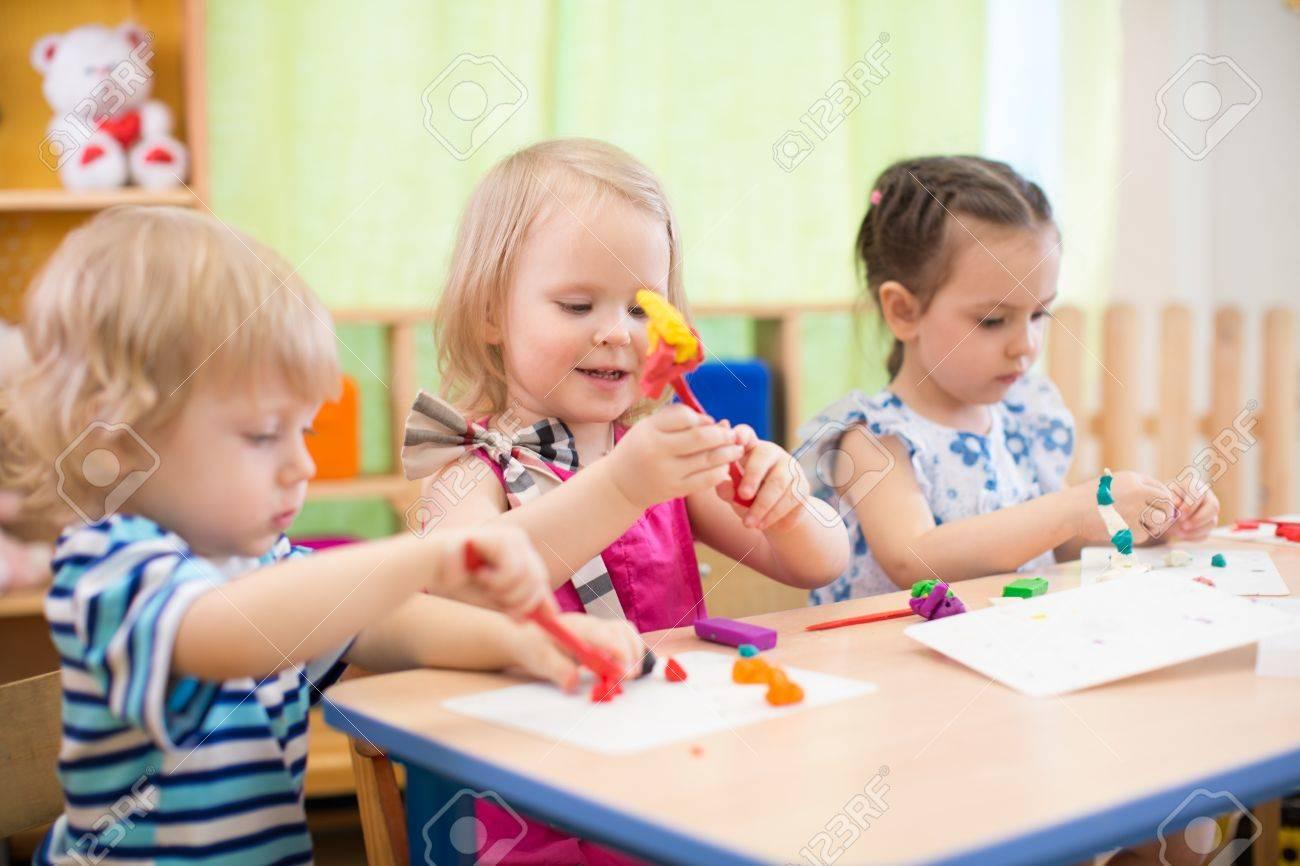 kids group making arts and crafts in kindergarten - 56494604