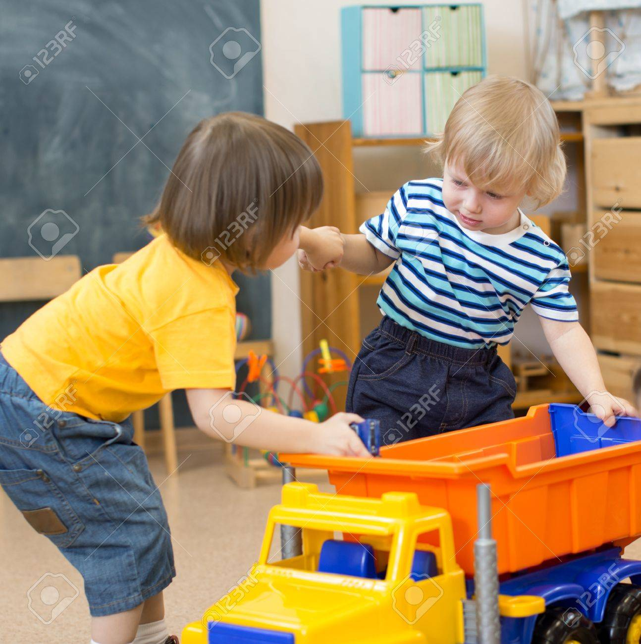 two kids pull toy truck in kindergarten play room each to his own side - 56495720