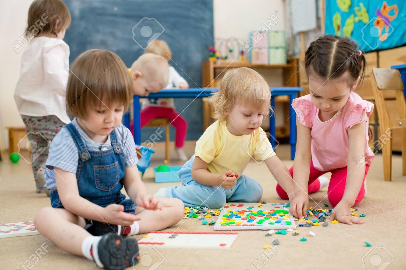 nios jugando el juego de grupo de mosaico en el jardn de infancia foto de archivo