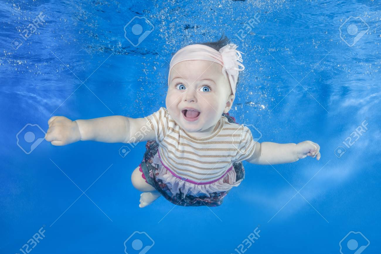c53ca16b5 Funny face portrait of little baby girl swimming and diving underwater..