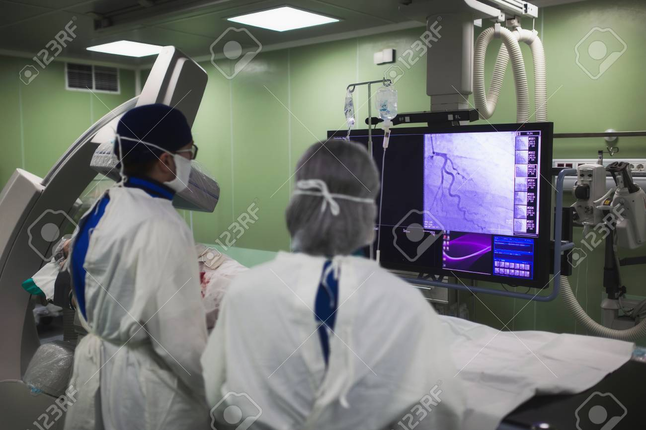 Doctors conduct a diagnostic operation. Coronarography. Percutaneous coronary intervention-recanalization, balloon angioplasty and stenting of the left coronary artery - 98105314