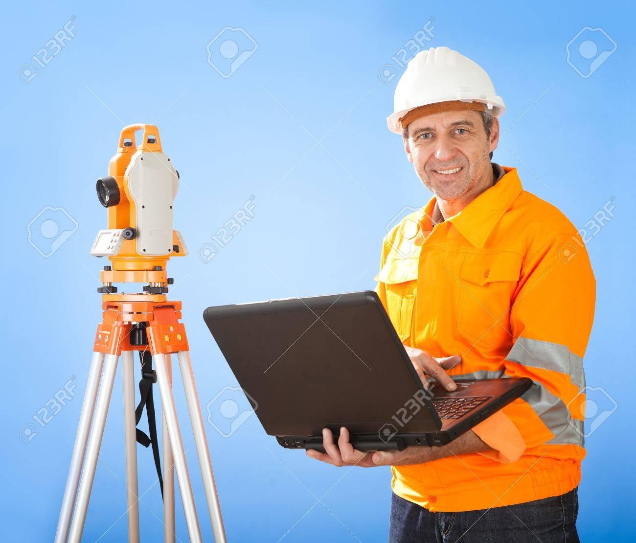 Portrait of Senior land surveyor working with theodolite at construction site Stock Photo - 12983559