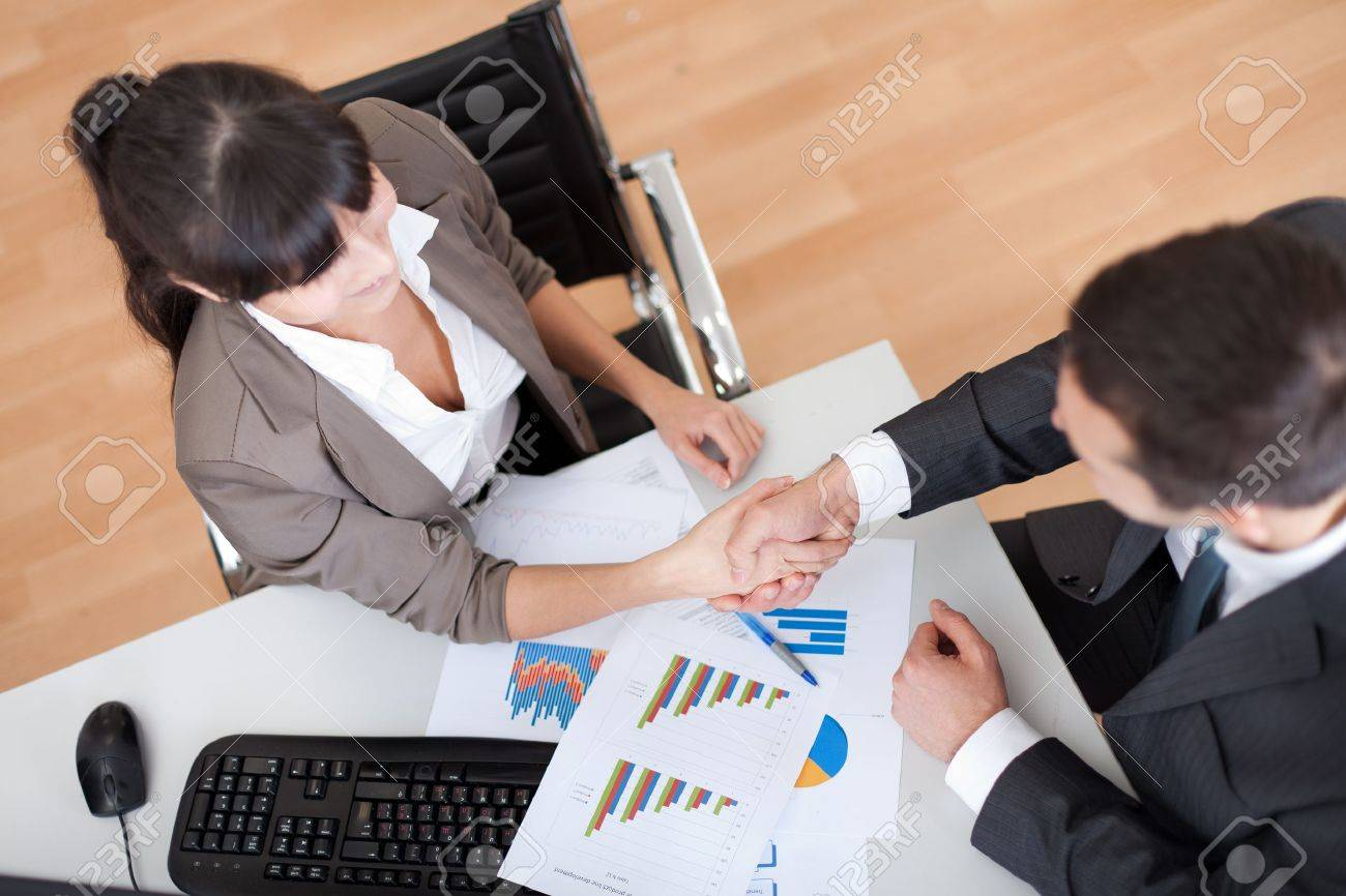 Two business people in the office at the meeting shaking hands Stock Photo - 13020568