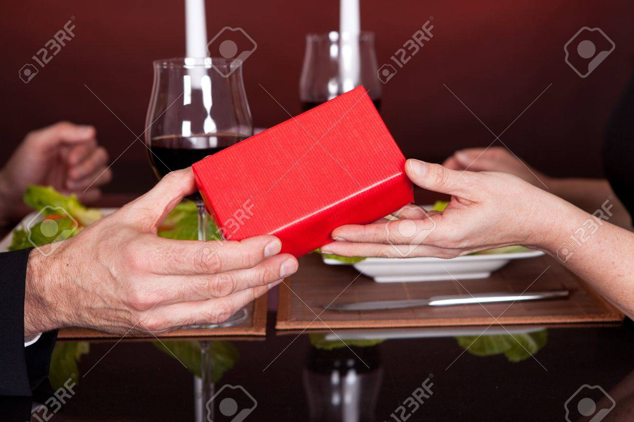 Man giving present to a woman at romantic dinner in restaurant Stock Photo - 13908076
