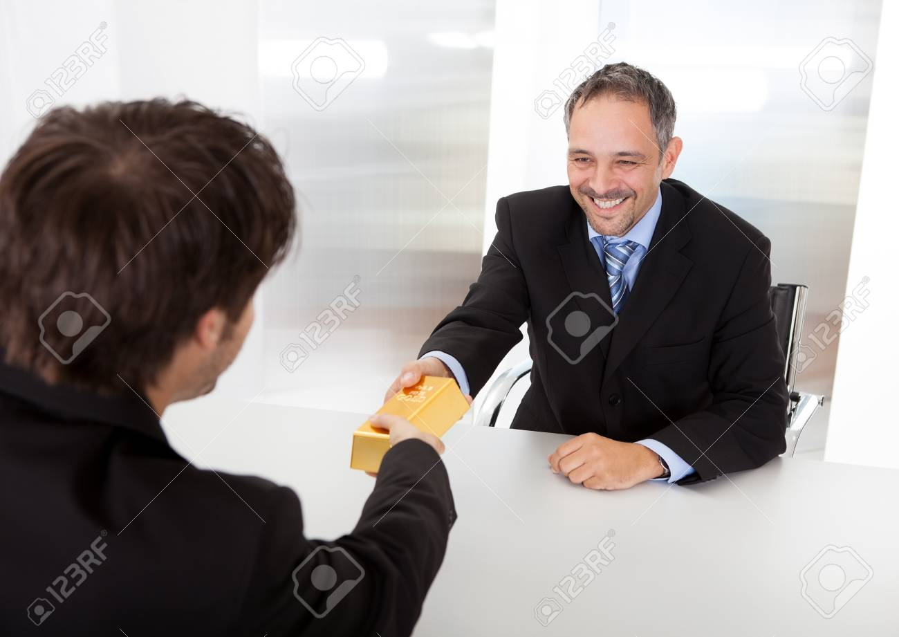 Portrait of happy businessman receiving gold bar Stock Photo - 14314064