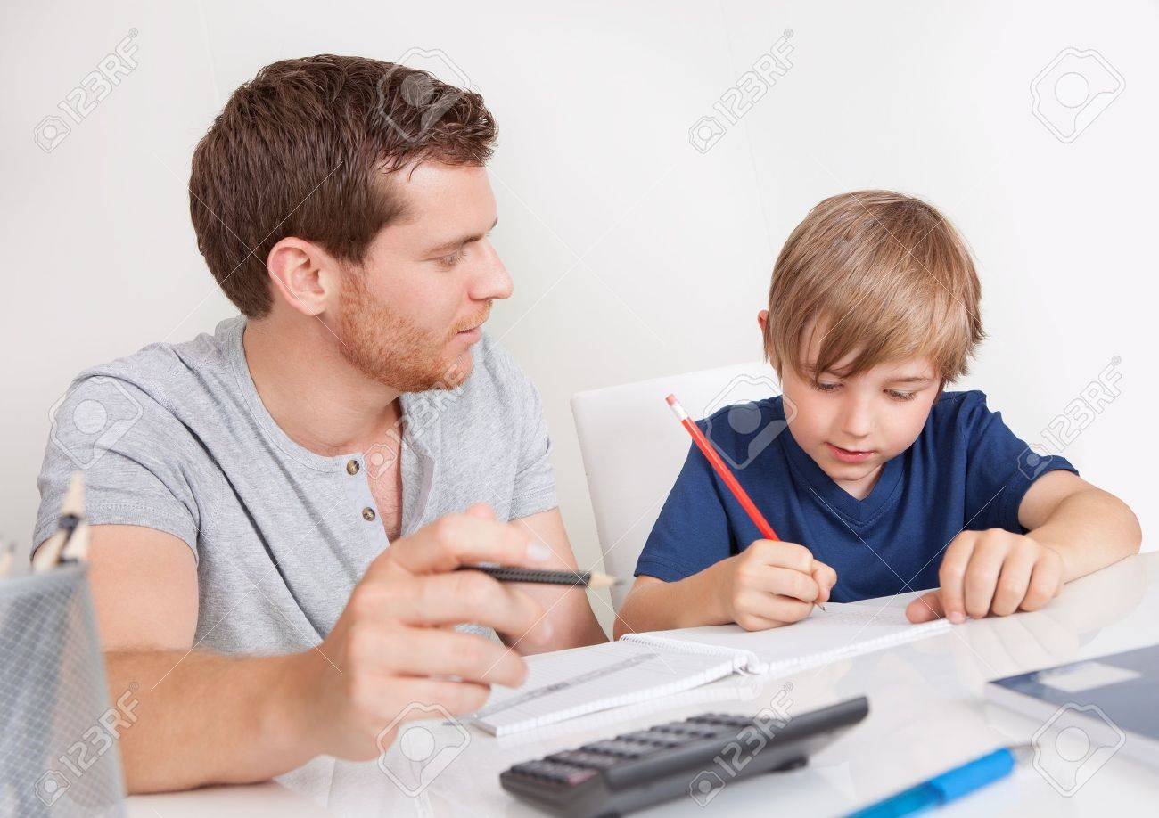 Young boy doing homework together with his father Stock Photo - 14976986
