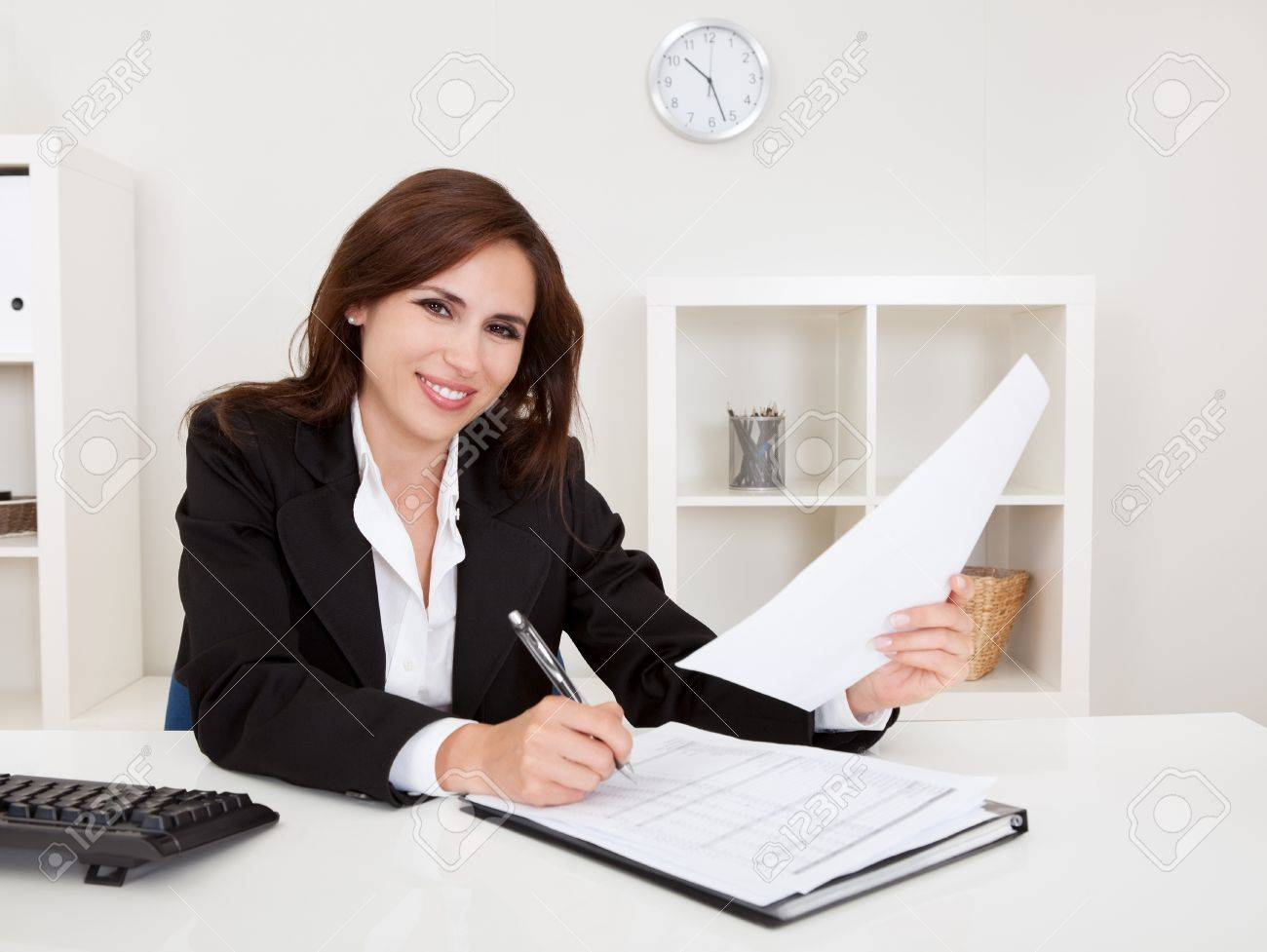Portrait of a businesswoman with paperwork at office desk Stock Photo - 15493580