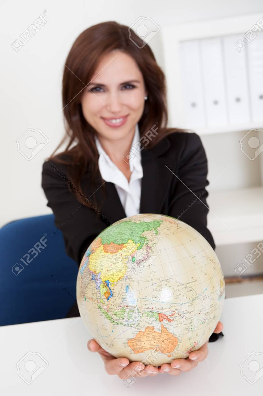 Portrait of a young businesswoman holding a globe in office Stock Photo - 15179524