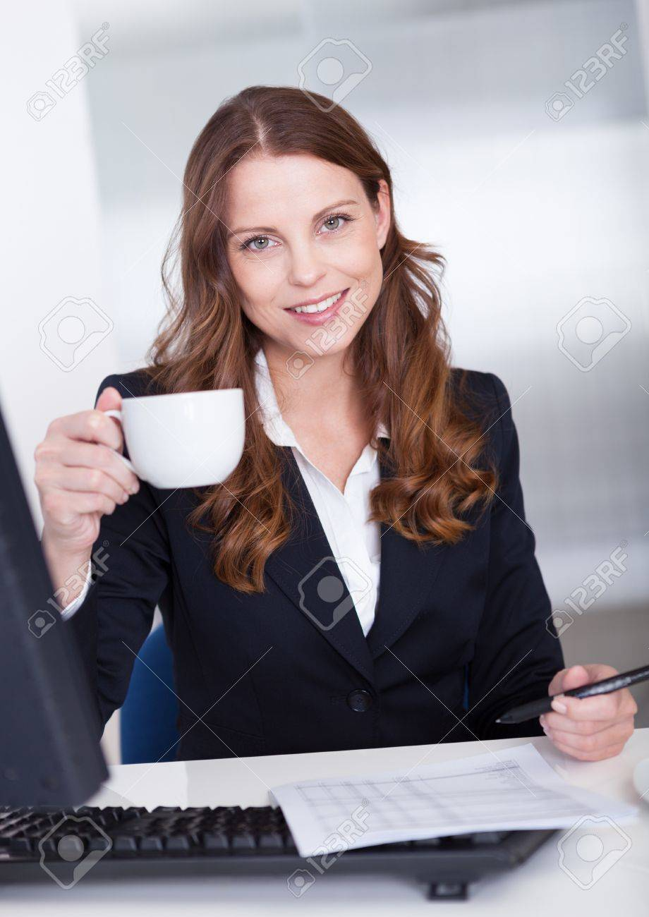 Smiling attractive businesswoman drinking a cup of tea or coffee while seated at her desk taking notes Stock Photo - 15175545