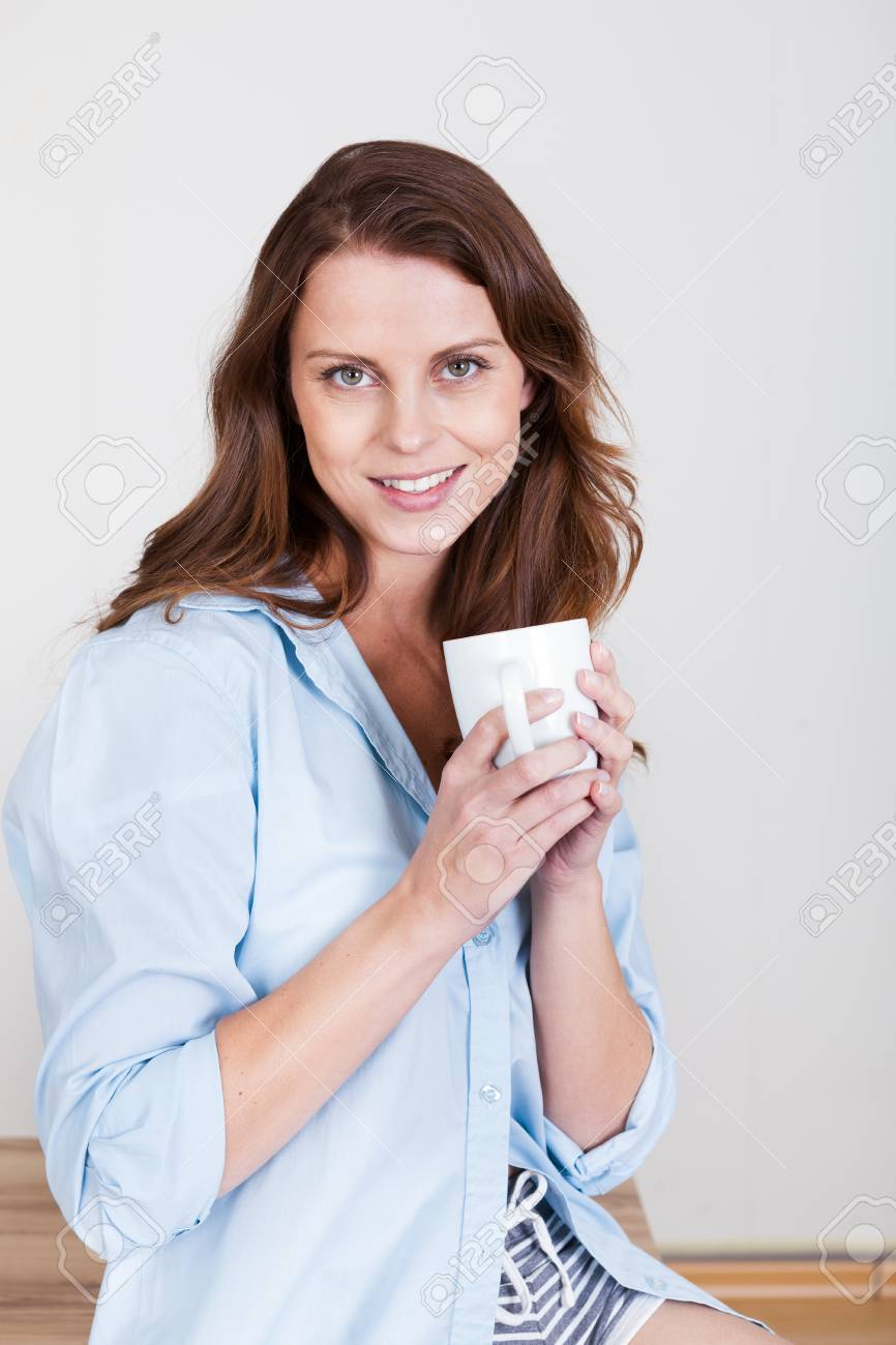 Beautiful young woman sitting indoors enjoying a cup of freshly brewed coffee Stock Photo - 15175676