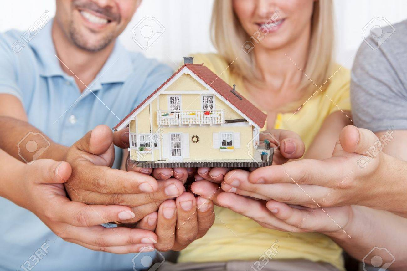 Happy parents with their teenage son and daughter holding a model house conceptual of setting a goal for home ownership Stock Photo - 15500697