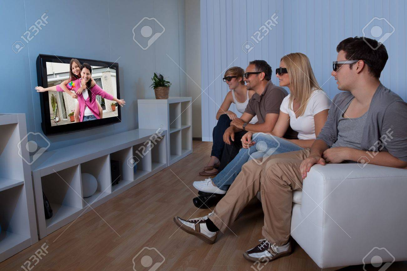 Family with teenage children sitting together on a couch eating bowls of popcorn wearing 3d glasses and watching the television Stock Photo - 15500717