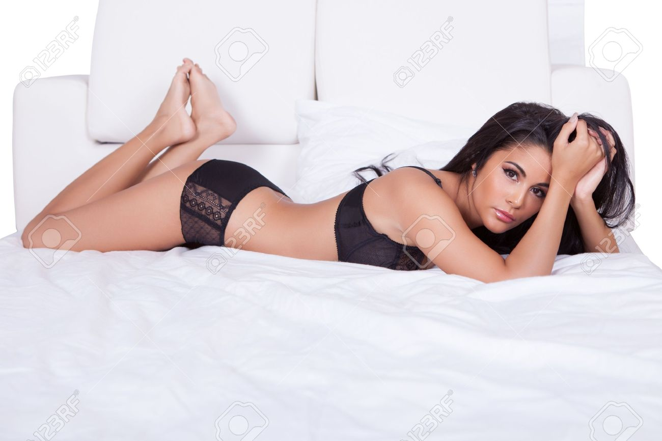 Beautiful sexy woman in black lingerie lying on her stomach on her bed with her feet in the air Stock Photo - 15512033