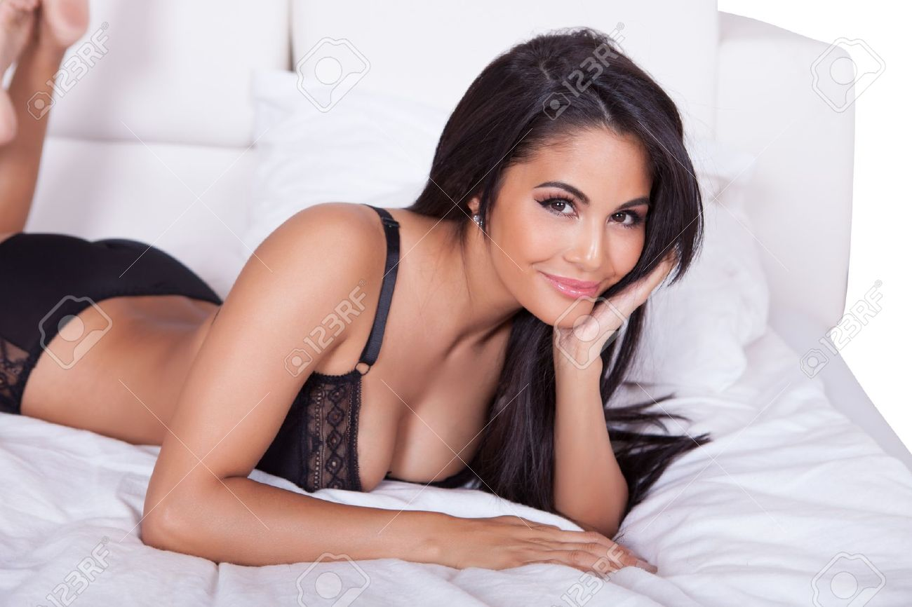 Beautiful sexy woman in black lingerie lying on her stomach on her bed with her feet in the air Stock Photo - 15512149