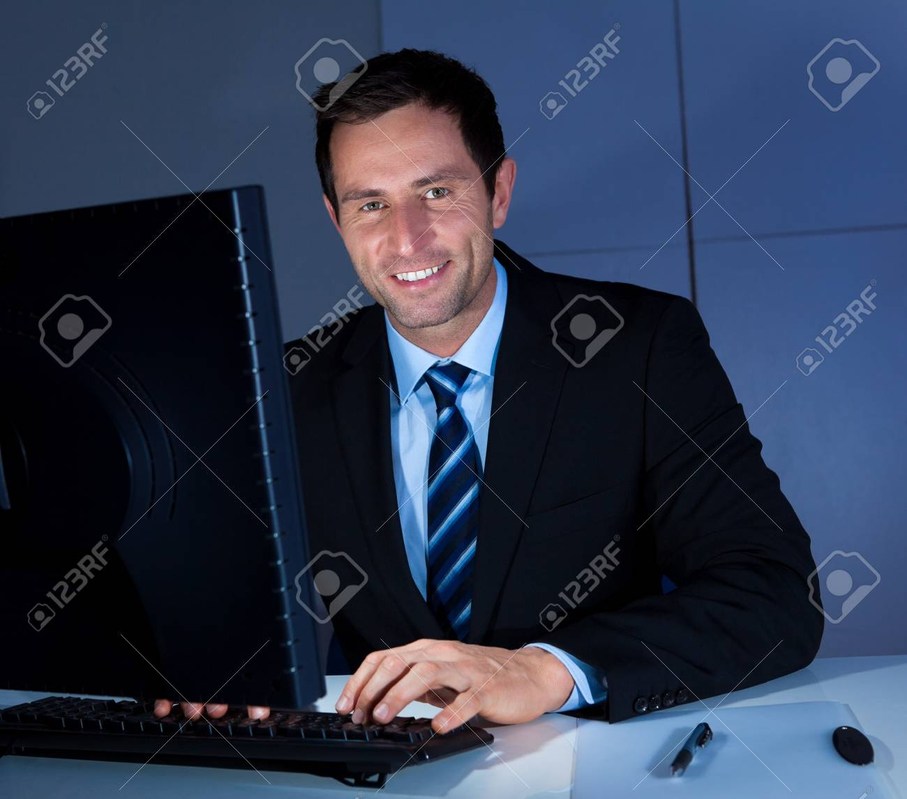 Portrait Of Happy Businessman Using Computer At Workplace Stock Photo - 15404161