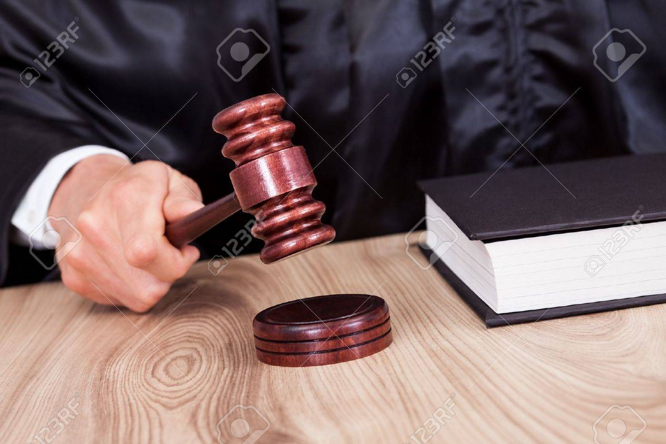 Male Judge In A Courtroom Striking The Gavel Stock Photo - 15403967
