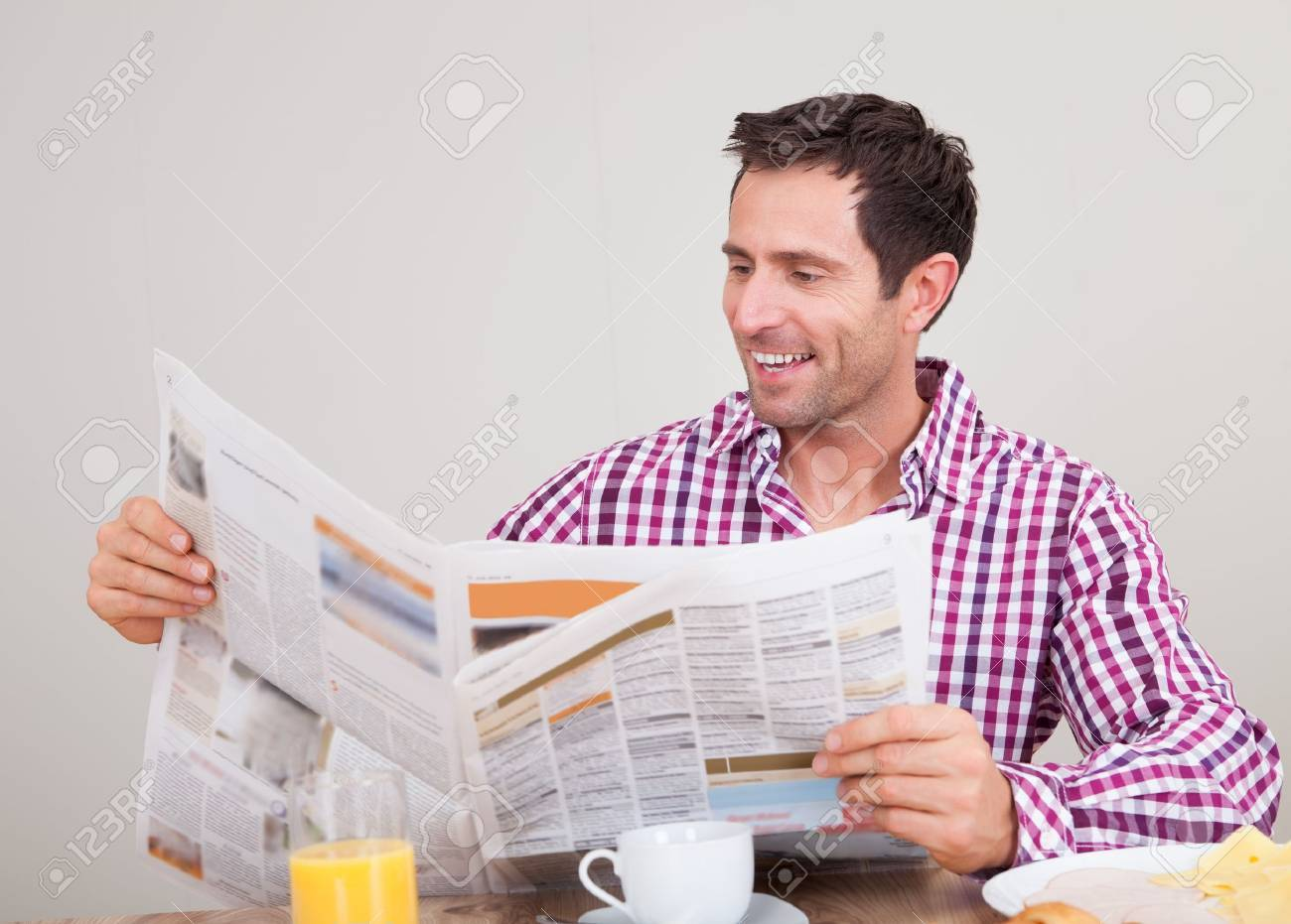 portrait of young man reading newspaper at breakfast, indoors stock