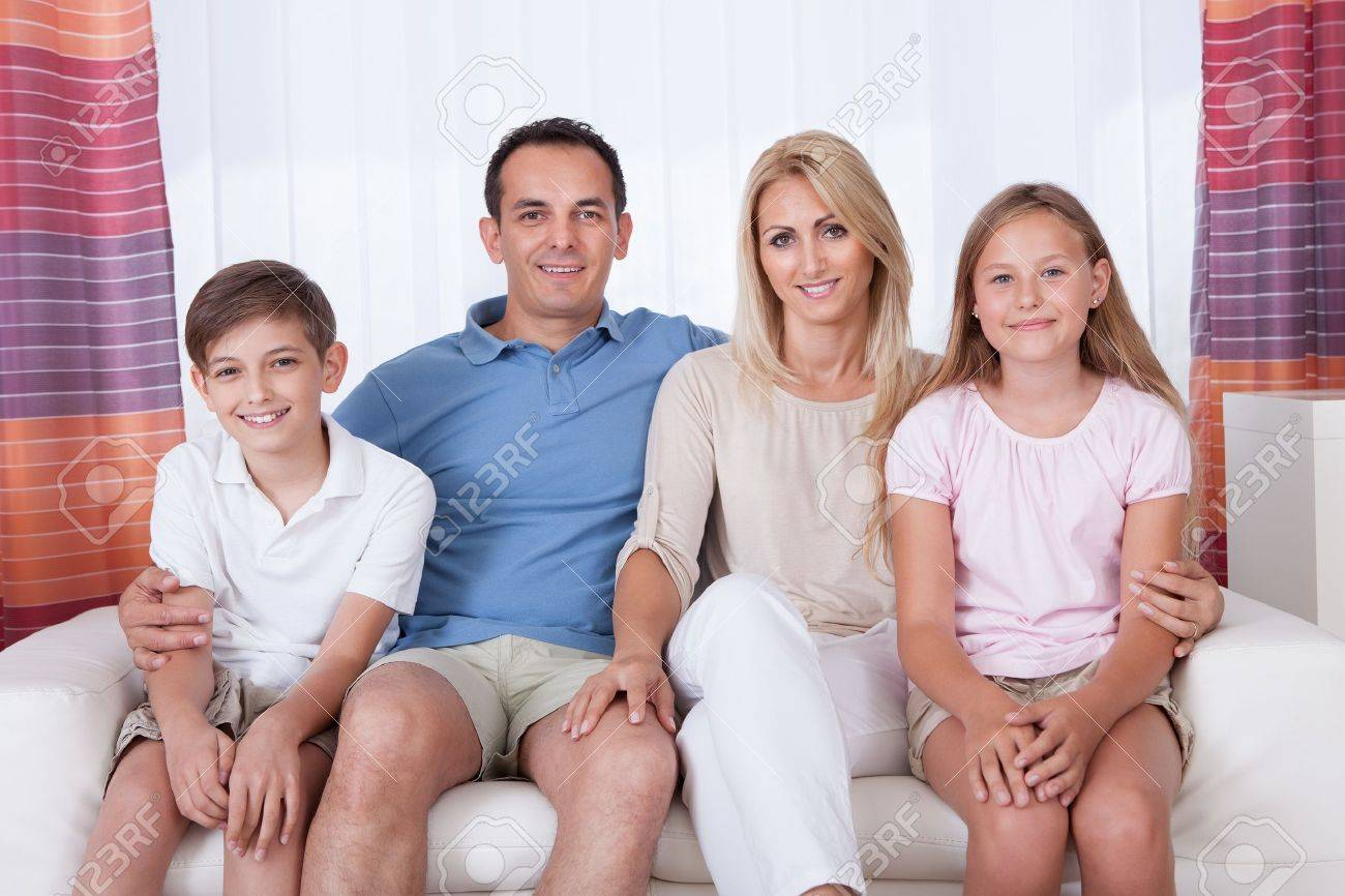A Happy Family With Two Children Sitting On Sofa At Home Stock Photo - 15574896