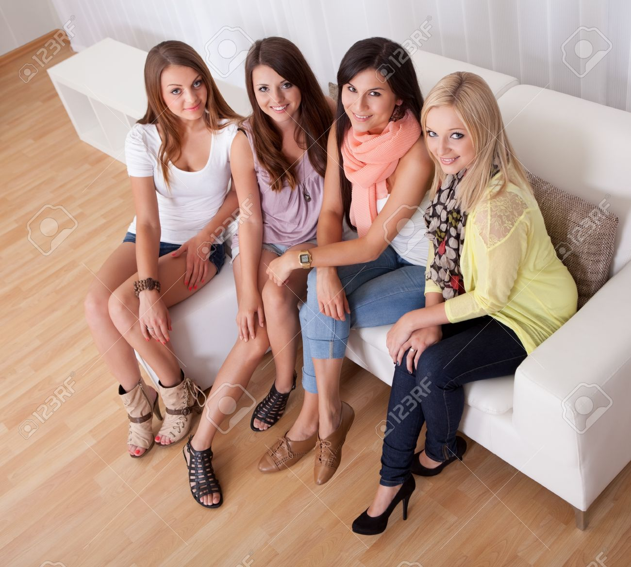 row of beautiful stylish young ladies sitting on a couch in a