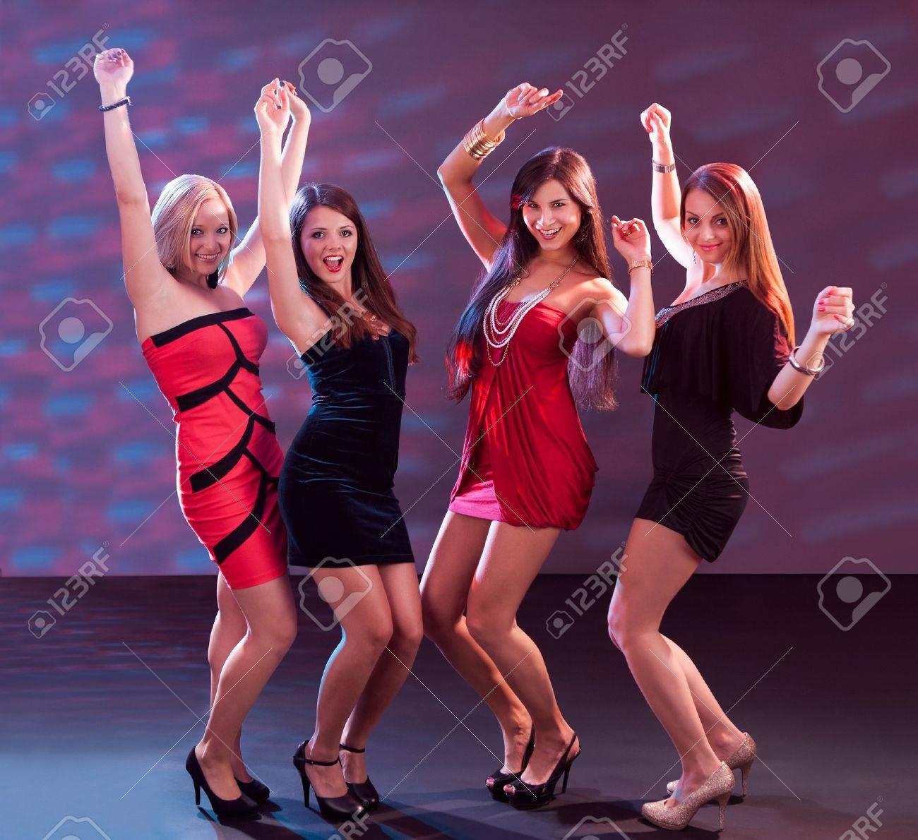 Grupo De Glamorosas Mujeres Jóvenes En Traje De La Tarde Bailando ...