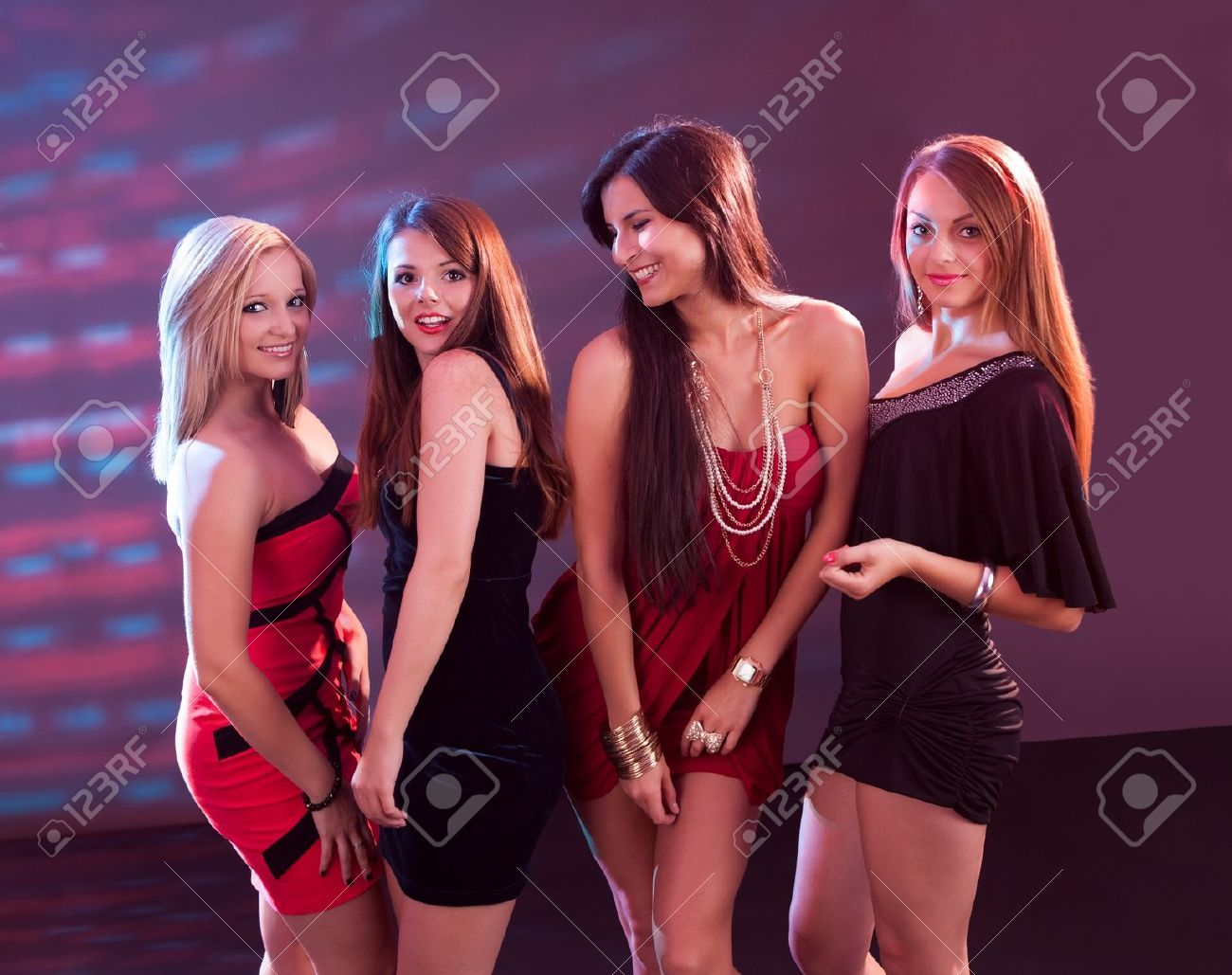 be883d1a8 Group of glamorous young women in evening attire dancing together at a  nightclub or disco Stock