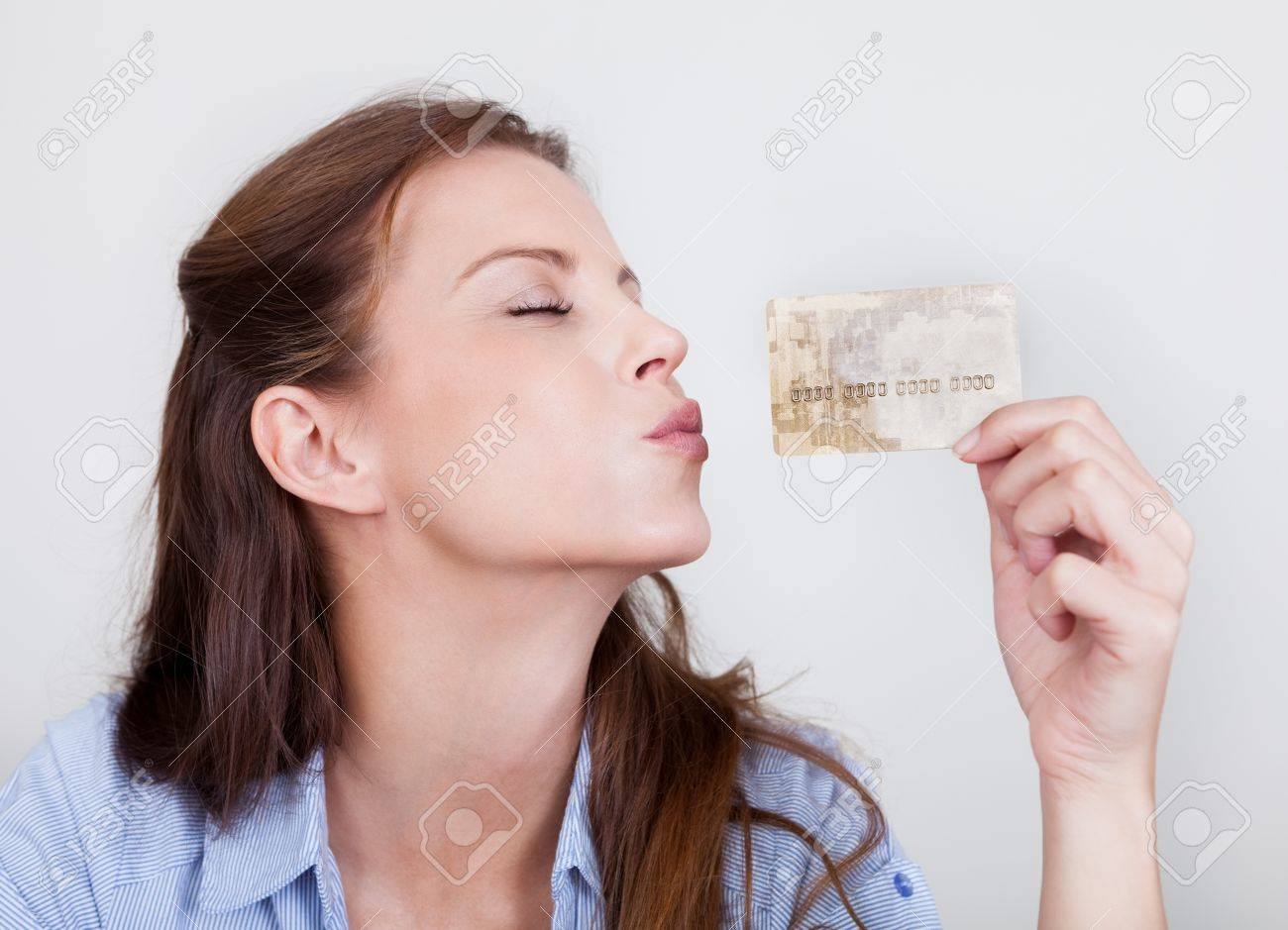 Young woman seated at her laptop entering her credit card details while shopping online Stock Photo - 16336687