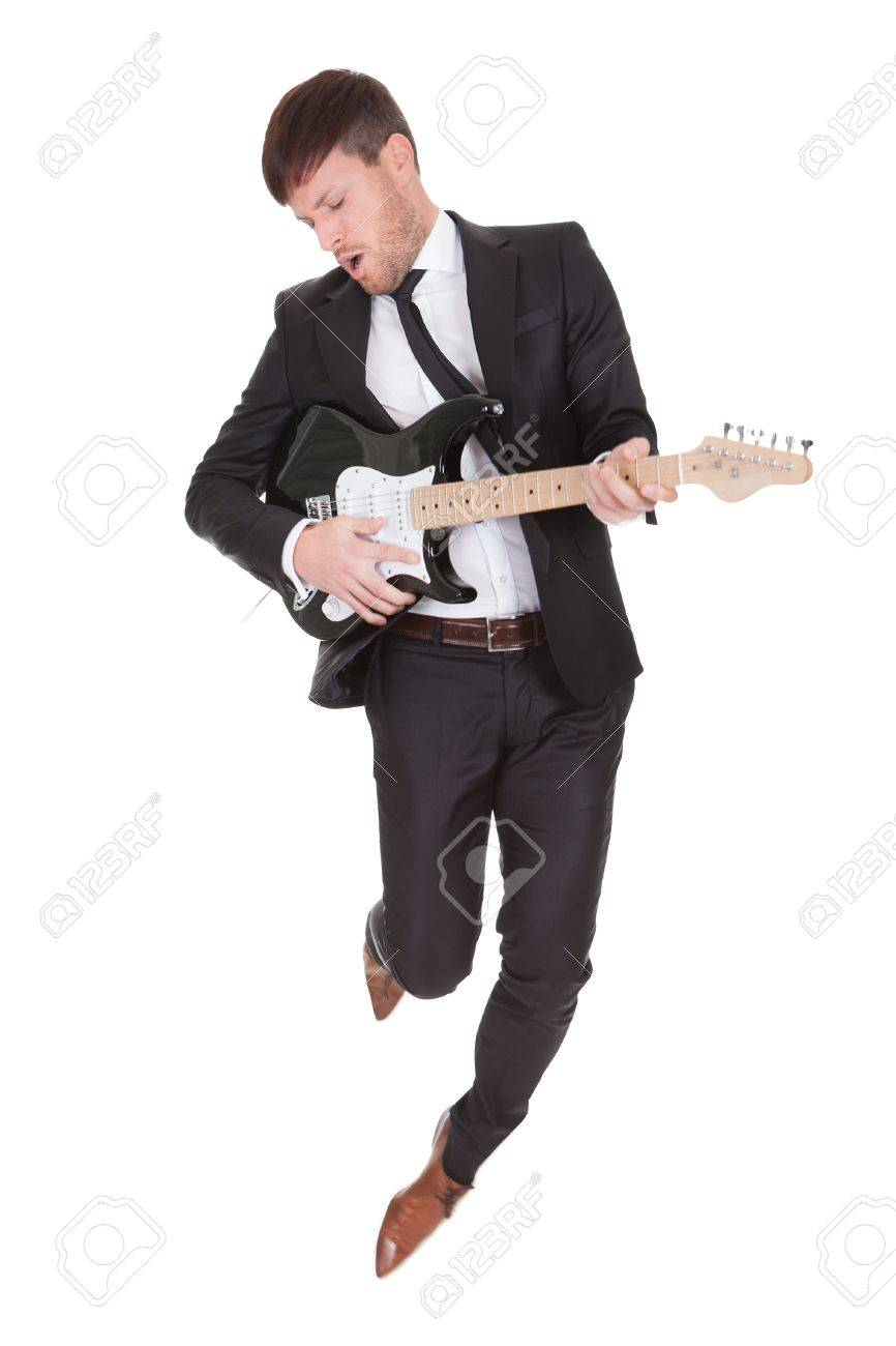 Elegant young man jumps while playing electric guitar Stock Photo - 16522701