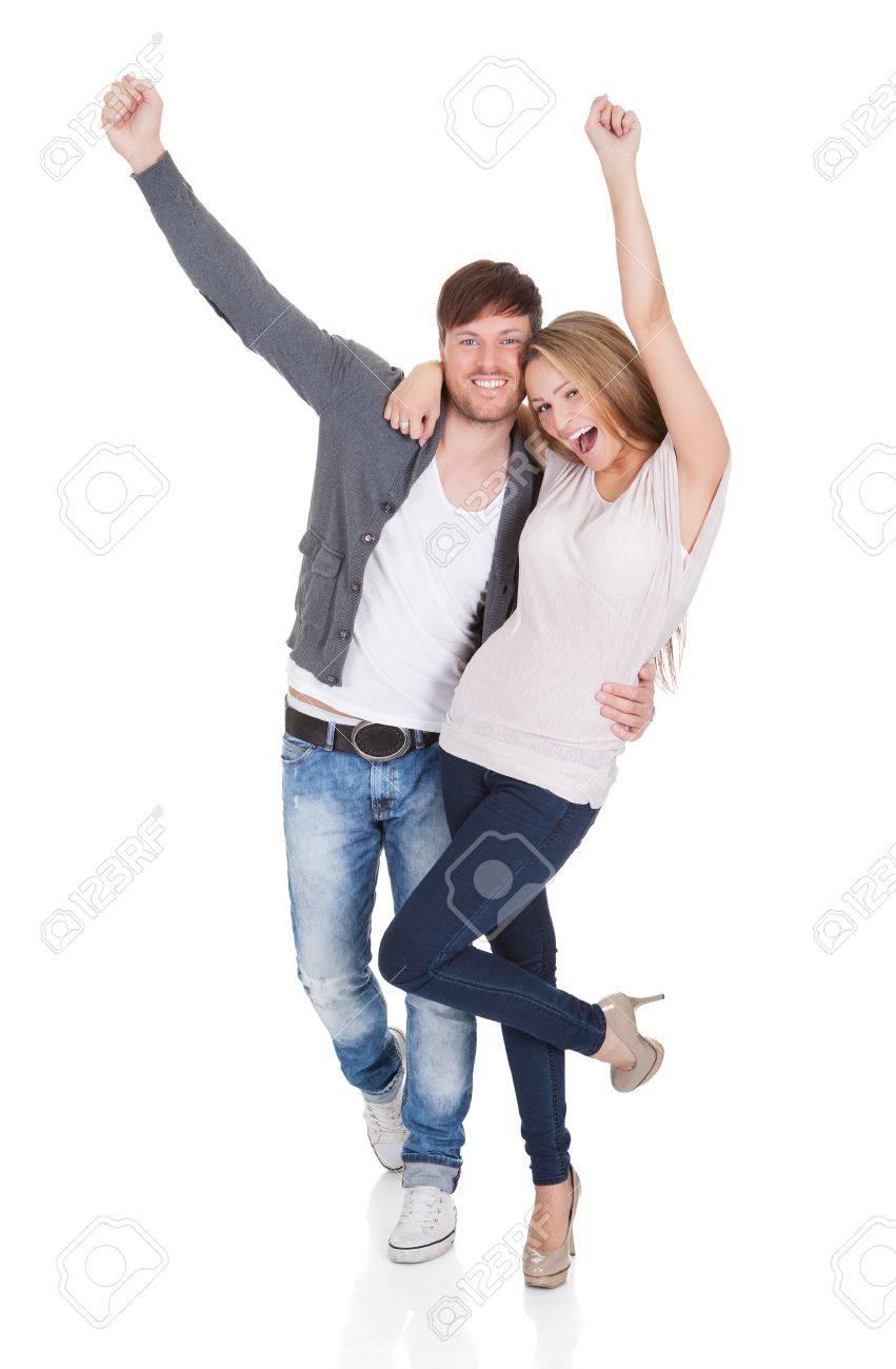 Premios Foroplural 16522673-Joven-pareja-feliz-de-pie-juntos-en-un-abrazo-amoroso-celebrando-y-riendo-golpes-al-aire-con-los-pu--Foto-de-archivo